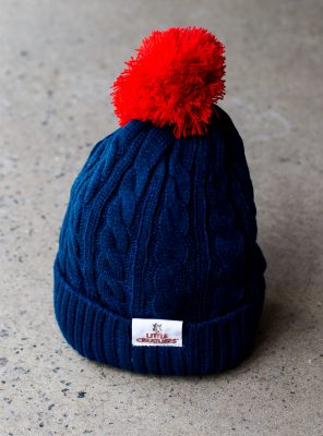 blue little creatures beanie with red pom pom